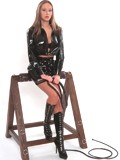 Madame Veronika in black pvc dress & lace-up boots